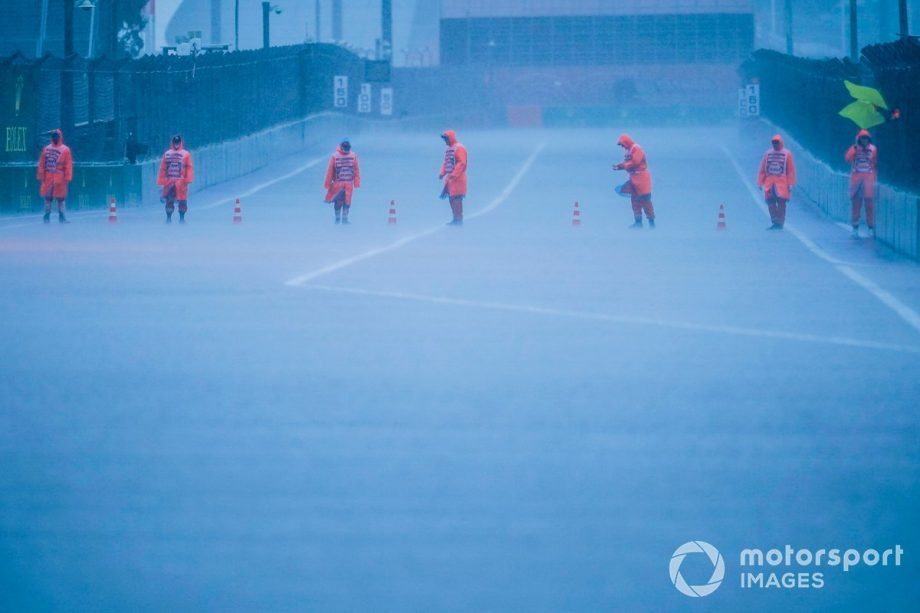 Stewards put out cones on the track as the rain falls